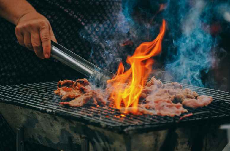 close up photo of man cooking meat